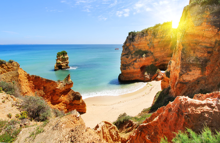Rocky beach at sunset, Lagos, Portugal. Counter light. Travel and business background Фото со стока