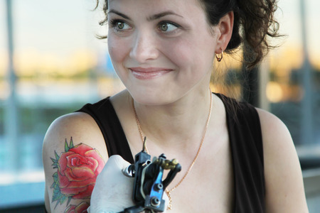tattooer showing process of making a tattoo on young beautiful hipster woman with red curly hair. Tattoo design in the form of rose. Vintage style picture