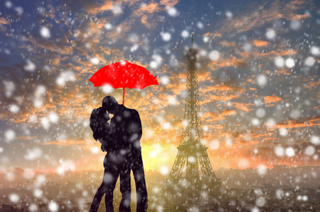 silhouette of couple standing in the snow storm under red umbrella with Eiffel tower in Paris , France on the background, abstract colorful romantic picture Stock Photo