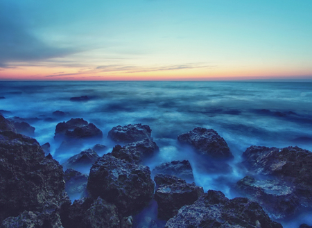 Seascape with sunset and rocks in a calm sea water. Soft focus Natural landscape