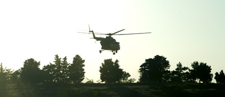 Silhouette of a military helicopter over the trees at sunset. Vintage colored picture Zdjęcie Seryjne