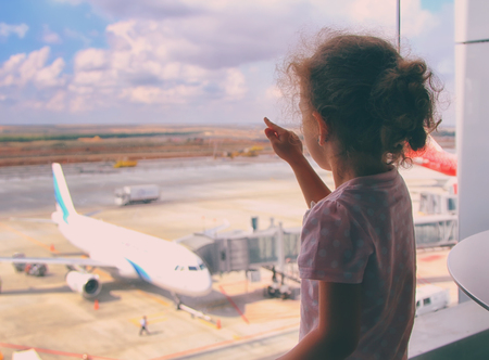 Little girl waiting for the plane at an airport. Child silhouette with the plane on the background Travel concept vintage colored picture