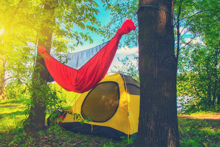 Yellow tent and hammock in the summer park Travel and adventure concept