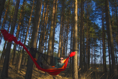 Tourist with sunglasses resting in a red hammock in a pine forest at spring sunset. Travel and adventure 版權商用圖片