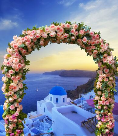 Wedding at Santorini. Beautiful arch decorated with flowers of roses with  blue church of Oia, Santorini, Greece at most romantic sunset in the world on the background. Wedding and honeymoon concept
