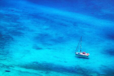 white yacht in azure blue bay with crystal clear water