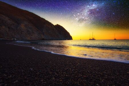 Galaxy over Perissa beach with Black volcano sand of at summer sunset.