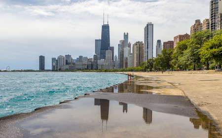 hancock: Chicago Illionois, US July 17 2016: Chicago Skyline and people bathing in Michigan lake on a hot summer afternoon Editorial