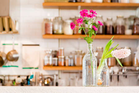 stocked: Flowers in two vases in a white kitchen with wooden shelves stocked with spices Stock Photo