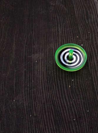 木製の背景に緑、白い、および黒の渦巻き模様紡績トップ