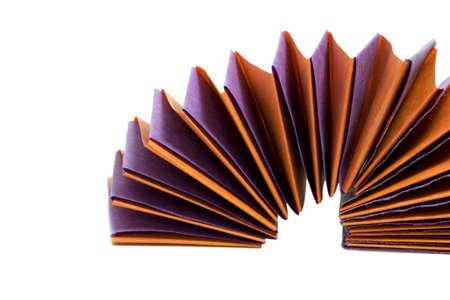 Purple and orange paper spring on white.