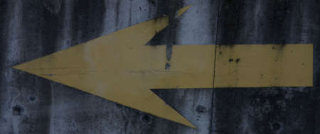 Yellow arrow painted on cement. Stock Photo