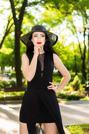 Portrait young woman in black dress and black hat walking in the park Stock Photo - 20382695