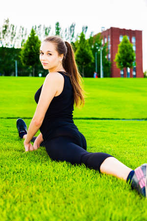 The young beautiful girl doing gymnastics outdoors photo