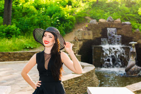 Portrait of a young beautiful woman in a hat and a black dress near fountain, in park  Stock Photo - 20382693