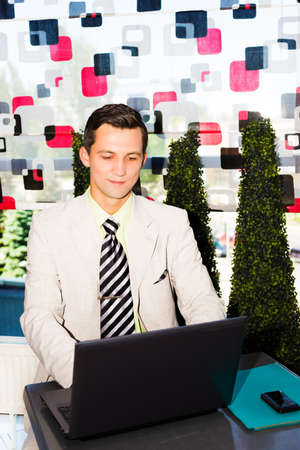 Businessman sitting in a cafe and working on his laptop photo
