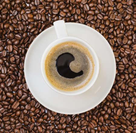 Cup der frischen schwarzen Kaffee über gerösteten Bohnen bedeckt Hintergrund