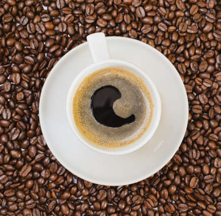 Cup of fresh black coffee over roasted bean covered background Stock Photo