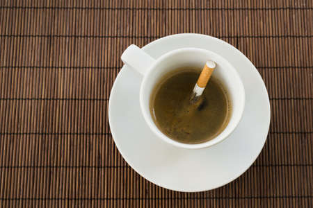 Cup of coffee with the cigarette inside, composition over a straw mat background photo