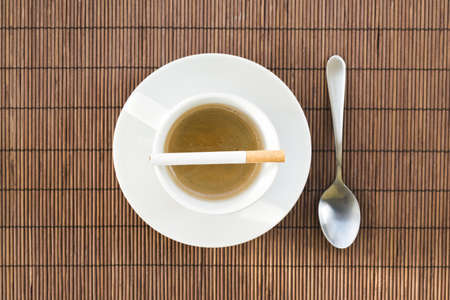 Cup of coffee and cigarette composition over a straw mat background photo