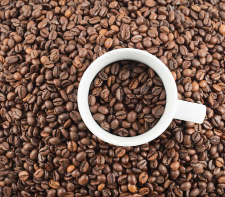 Cup full of coffee bean over covered with beans flat surface as abstract background