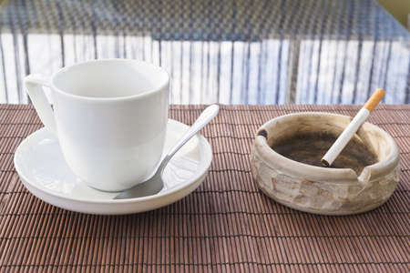 Cup of coffee and cigarette ashtray composition over a straw mat background photo