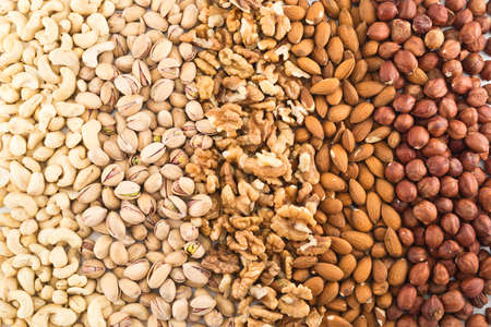 Surface covered with different nut mix of hazelnut, pistachio, peanut, almond, walnut as a food background photo
