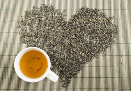 Black tea heart shape over bamboo mat topview with teacup photo