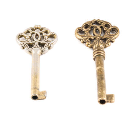 Old decorative metal keys isolated over white background, set of two photo