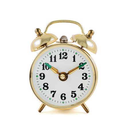 speed of sound: Traditional wind-up keywound, spring-driven mechanical golden alarm clock isolated over white background, front view