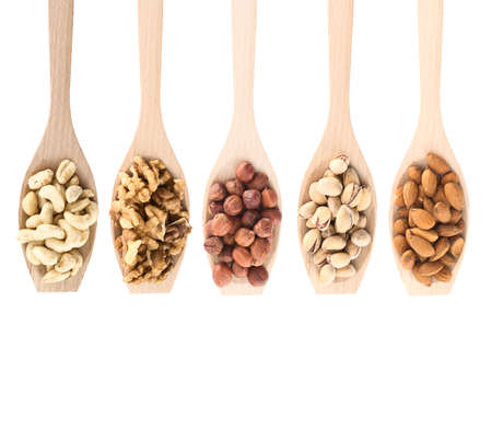 walnuts: Wooden spoons full of different kinds of nuts: peanut, hazelnut, walnut, almond, pistachio, isolated over white background, top view