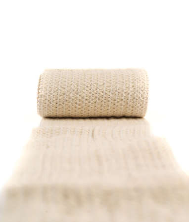 Elastic ACE compression bandage warp unwrapped over white background, shallow depth of field Stock Photo