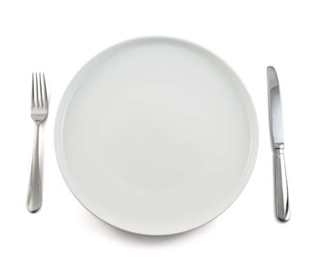 Dinner is served composition: table knife and fork next to the ceramic empty copyspace plate dish isolated over white background, top view photo