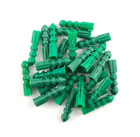Green plastic dowel pin pile isolated over white background, above close-up photo