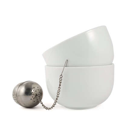 Two ceramic piola bowls with a tea strainer isolated over white background photo