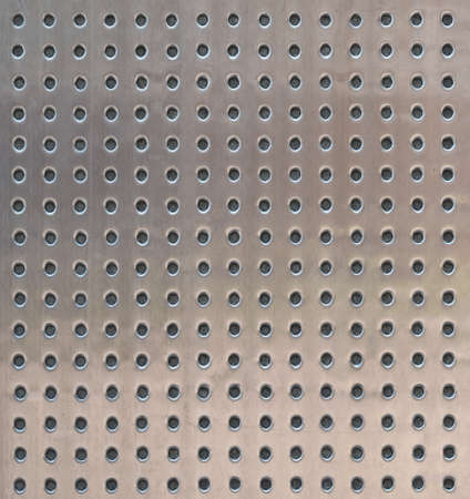 Perforated metal surface texture as an abstract background