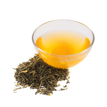 Glass bowl of tea next to a pile of dried green leaves, isolated over white background