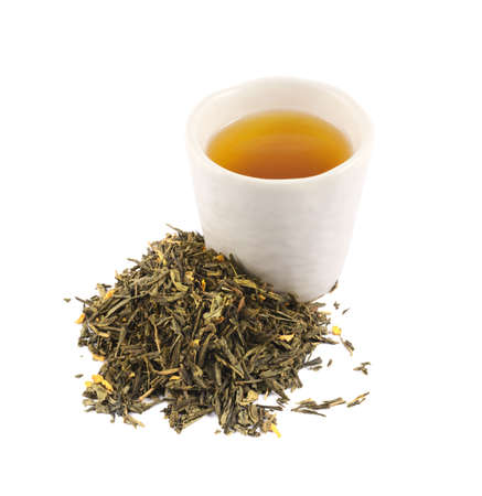 Ceramic cup of tea next to a pile of dried green leaves, isolated over white background