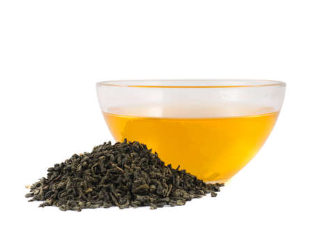 Glass bowl of tea next to a pile of dried green leaves, isolated over white background Stock Photo - 20496805