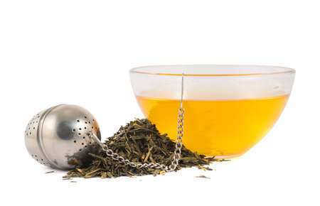 Glass piola bowl of tea next to metallic infuser and a pile of dried leaves isolated over white background photo