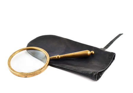 Old authentic magnifying glass over a black leather case isolated against the white background