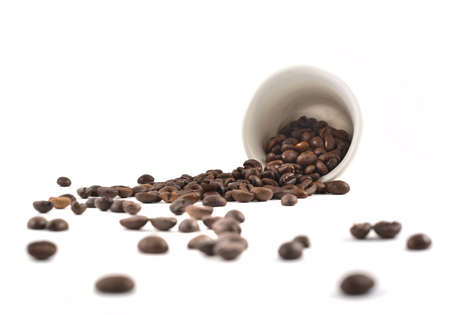 Spilled coffee beans from the white ceramic cup isolated over white background photo