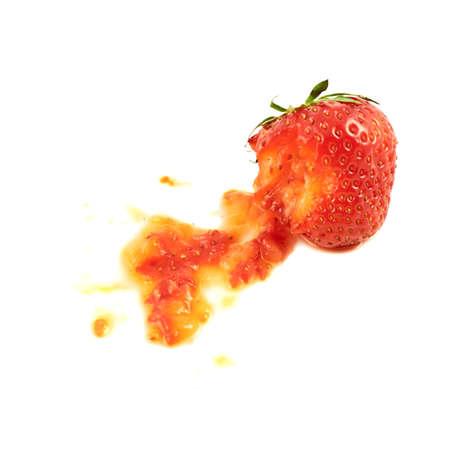 Squashed strawberry isolated over white background photo