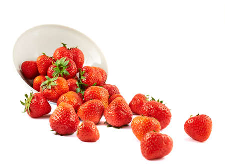 pile of leaves: Scattered strawberries from a white ceramic bowl isolated over white background Stock Photo