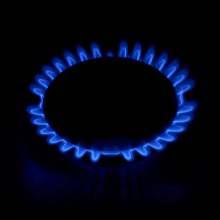 Gas stove as a blue fire lights in the dark