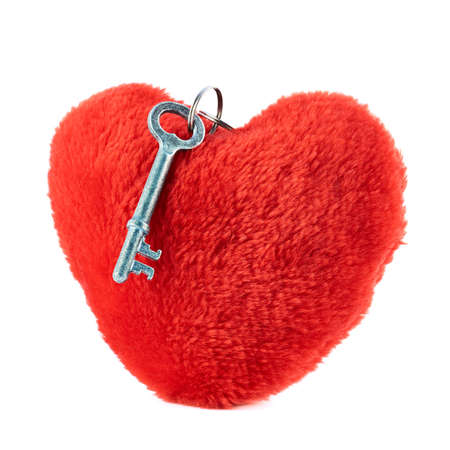 Metal key over a red plush heart isolated against white background photo