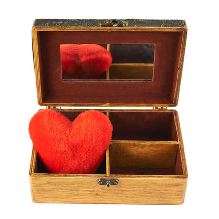 Plush heart in a wooden casketPlush red heart in a old-fashioned wooden old casket with a mirror isolated over white background