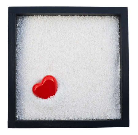 Red heart shape in a white sand copyspace background photo