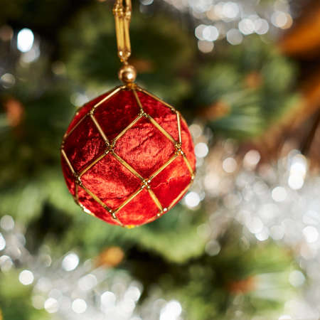 Seasonal Christmas decoration background of a decorational ball over a defocused fragment of xmas tree