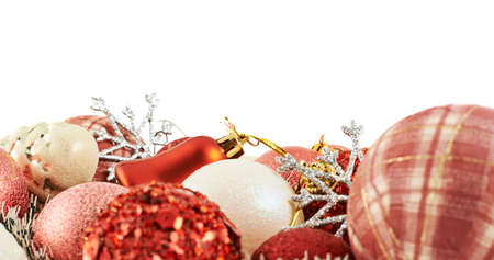 Seasonal Christmas decoration background as a pile of xmas tree decorations over white background photo
